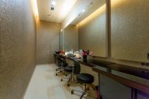벽에 큰 거울이 있고 그 앞에 까만 긴 테이블과 원형 의자가 줄 지어있다.